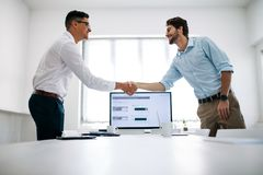 Business partners shaking hands in office Stock Images