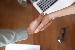 Business partners shaking hands over table after meeting. Top view stock images
