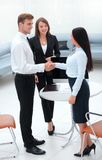 Business partners shaking hands while standing in the lobby of the office. Stock Images