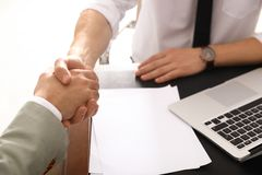Business partners shaking hands at table after meeting. In office, closeup royalty free stock image