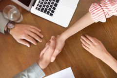 Business partners shaking hands at table after meeting. Top view royalty free stock images