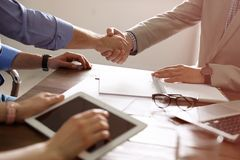 Business partners shaking hands at table after meeting in office. Closeup stock photography