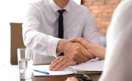 Business partners shaking hands at table after meeting in office. Closeup royalty free stock images