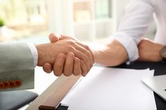 Business partners shaking hands at table after meeting in office. Closeup royalty free stock photos