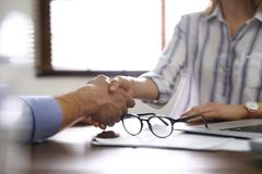 Business partners shaking hands at table after meeting in office. Closeup royalty free stock image