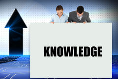 Business partners showing card saying knowledge Royalty Free Stock Image
