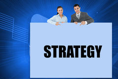 Business partners showing card saying strategy Royalty Free Stock Photo
