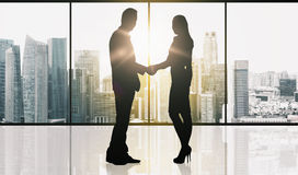 Business partners silhouettes making handshake. Business, teamwork, partnership, cooperation and people concept - partners shaking hands over office window and Royalty Free Stock Photo