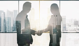 Business partners silhouettes making handshake. Business, teamwork, partnership, cooperation and people concept - partners shaking hands over office window and Royalty Free Stock Photography