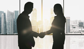Business partners silhouettes making handshake. Business, teamwork, partnership, cooperation and people concept - partners shaking hands over office window and Stock Image