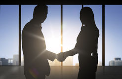 Business partners silhouettes shaking hands. Business, teamwork, partnership, cooperation and people concept - business people shaking hands over office Stock Images