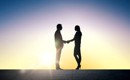 Business partners silhouettes shaking hands Stock Photos
