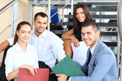 Business partners sitting on stairs in office Stock Photo