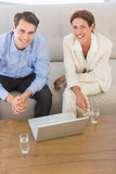 Business partners smiling at camera sitting on sofa Royalty Free Stock Photos