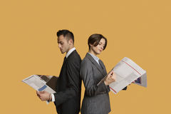 Business partners standing back to back while reading newspaper Royalty Free Stock Images