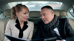Business partners talking in the backseat of a car stock footage