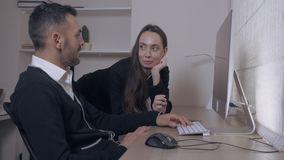 Business partners talking in office. Two people looking on display computer discussing some project. attractive caucasian businesswoman standing near working stock video footage