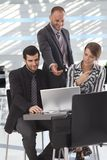 Business partners talking over laptop in lobby Royalty Free Stock Images