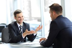 Business partners talking while sitting at your Desk Royalty Free Stock Photos