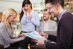 Business partners talking and working in coffee bar Stock Image