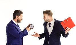 Business partners with tense faces argue about deadline. Businessman in classic suit holds clock and his partner holds red folder. Business and discipline royalty free stock photos