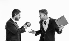 Business partners with tense faces argue about deadline. Businessman in classic suit holds clock and his partner holds red folder. Business and discipline stock photos