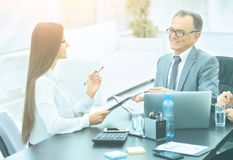 Business partners to discuss cooperation plan for the workplace. Business partners to discuss a plan of cooperation in the workplace, discussion leader and Royalty Free Stock Images