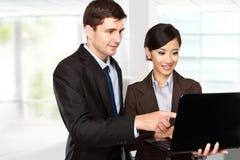 Business partners using laptop at meeting. Image of two young business partners using laptop at meeting Stock Photos