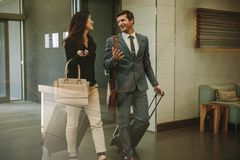 Business partners walking through airport lobby. With their luggage and having a chat. Business people going on a business trip Royalty Free Stock Photo