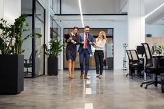 Business partners walking down in office building and discussing work Stock Images