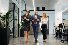 Business partners walking down in office building and discussing work Stock Photo