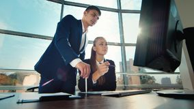 Business partners work together in a large bright and modern office. Two young men working with tablet. Against the backdrop of a large window stock video