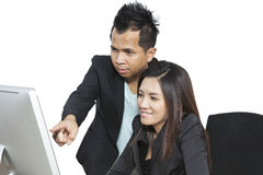Business partners working at the office on a computer. Happy coworkers working together, discussing work Stock Photos