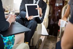 Business Partners Working In Private Jet. Businessman showing project on digital tablet to partners in private jet Royalty Free Stock Photography