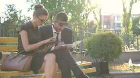 Business partners working on tablet computer and notebook on bench. 4K.  stock footage