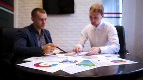 Business partners working together. Teamwork over statistics with graphs. Business meeting stock video footage