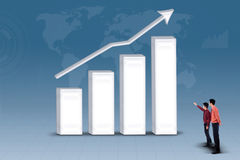Business partnership looking at increasing bar chart. Business partnership are looking at increasing bar chart on blue background Royalty Free Stock Photography