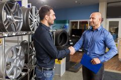 Auto business owner and wheel rims at car service. Business, partnership and people concept - male customer and salesman shaking hands at car repair service or stock photography
