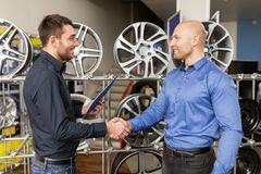 Auto business owner and wheel rims at car service. Business, partnership and people concept - male customer and salesman shaking hands at car repair service or Royalty Free Stock Photos