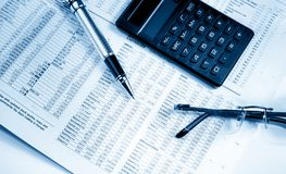 Business pen, calculator and glasses on currencies newspaper Royalty Free Stock Photos
