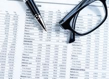Business pen and glasses on currencies newspaper Stock Images