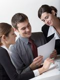 Business people. Bussinessman and two businesswomen working at office Stock Image