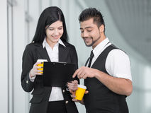 Business People. Confident businesswoman and businessman standing in office and drink coffee Royalty Free Stock Photo