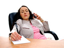 Business People 4. Serious business woman at her desk talking on cellphone and taking notes royalty free stock photography