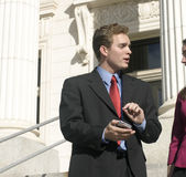 Business people. Businessman is facing businesswoman pointing to pda while talking on steps of courthouse Stock Photo
