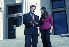 Business people. Businessman and businesswoman standing looking down at pda on courthouse steps Royalty Free Stock Photos