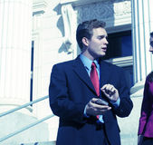 Business people. Businessman is facing businesswoman pointing to digital assistant while talking on steps of courthouse Royalty Free Stock Photography