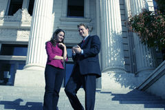 Business people. Businessman and businesswoman standing looking down at pda on courthouse steps Stock Images
