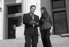 Business people. Businessman and businesswoman standing looking down at pda on courthouse steps Royalty Free Stock Photo