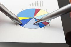 Business people analyzing market report on pie chart.  Stock Photos